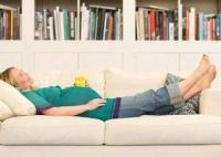 kanapén fekvő terhes nő, visszeresség, visszértágulat, terhesség